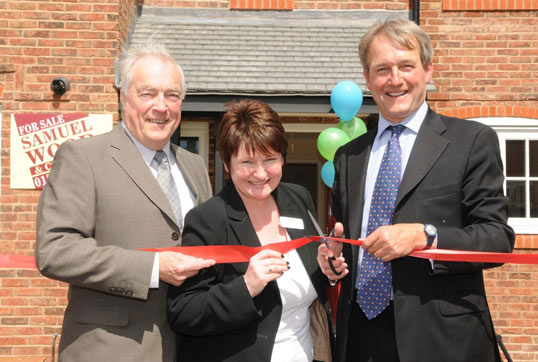 Owen Paterson MP (right), cuts the ribbon to open the Village Green development, with MMHA board member, Gordon Hodgkiss and managing director, Jennie Barfoot